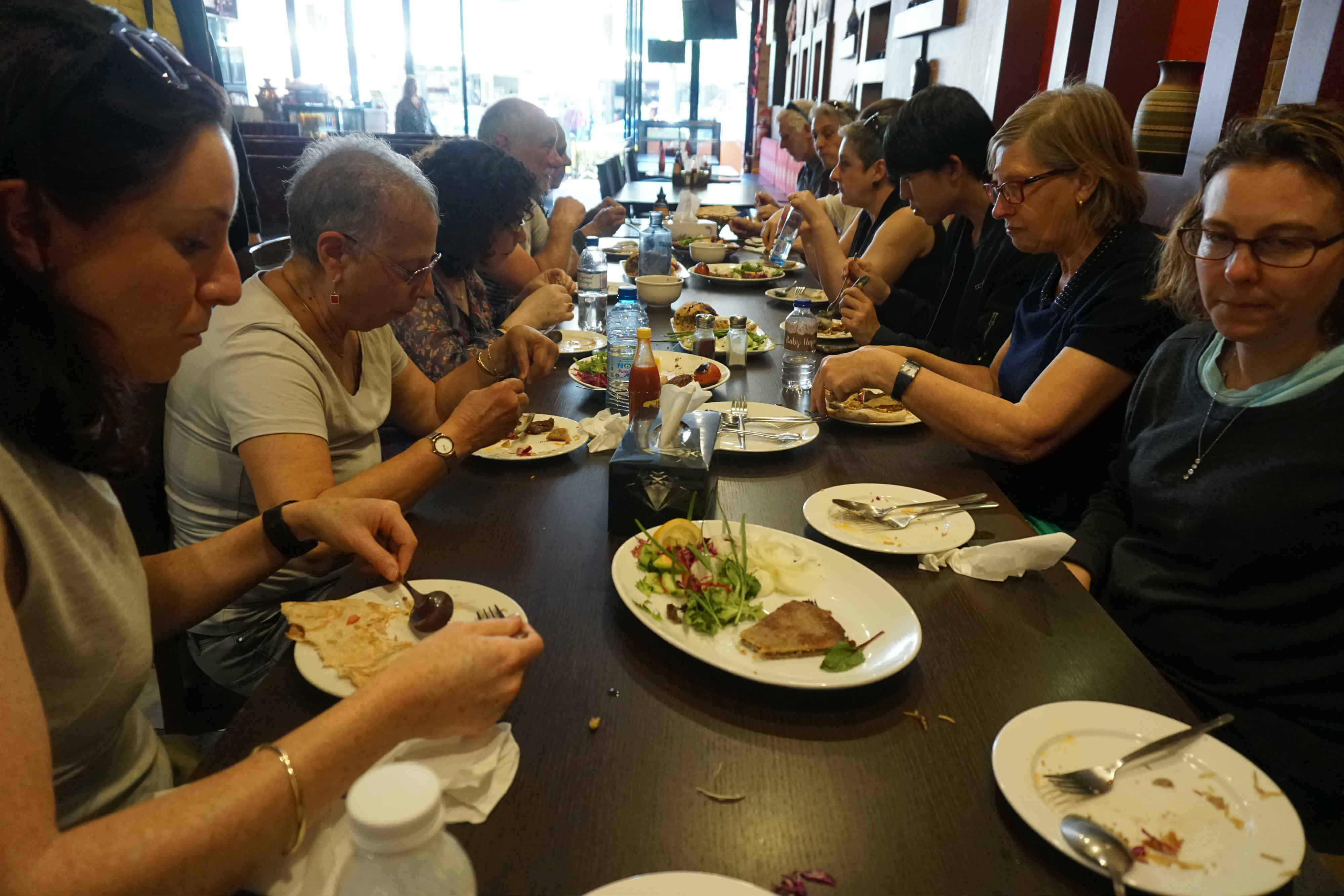 Customers enjoying a typical Persian meal in a traditional decorated Persian restaurant.